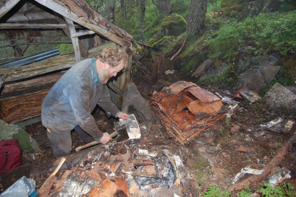 Håndverker Arne Vassenden arbeider her med neverflakene som skal brukes i taktekkingen av Jedlaløo. (Foto: Kulturminnefondet)