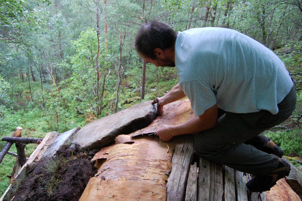 Håndverker Trond Oalann legger velessesteiner ytterst på takflata mot gavlene på Jedlaløo. (Foto: Kulturminnefondet)