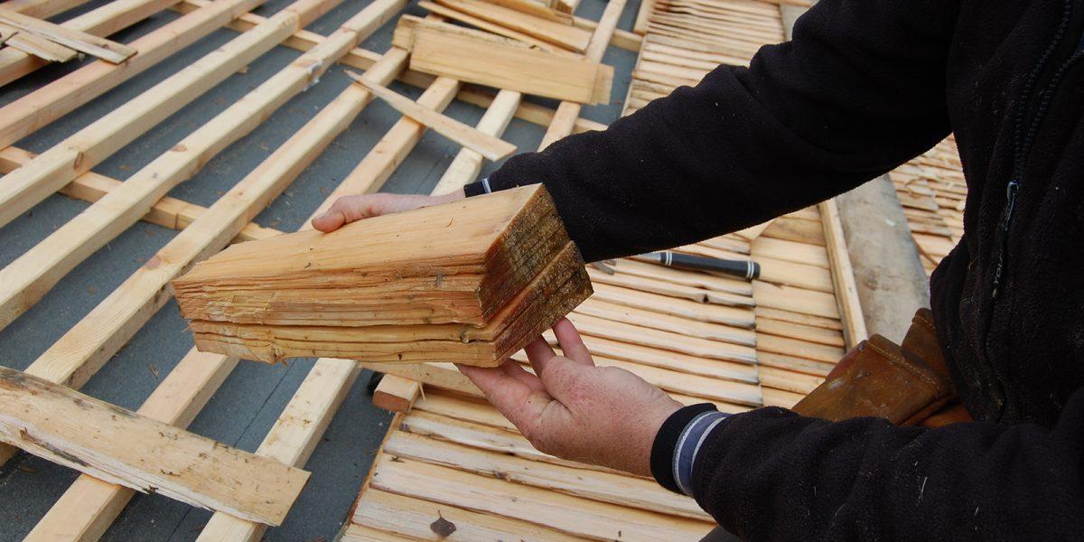 Taket var lagt med innstikksida ned. Her vurder håndverkeren stikkeretning og forbereder spikring. (Foto: Einar Engen, Kulturminnefondet)
