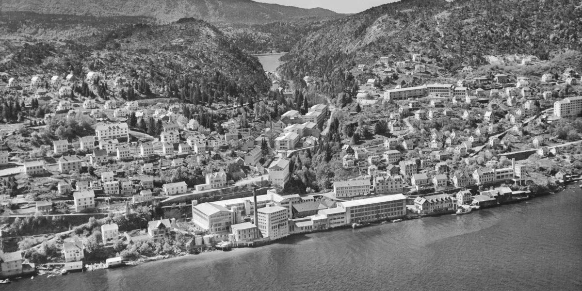 Den første ullvarefabrikken hos Arne fabrikker ble bygget nede ved fjorden i 1852, men samme år brant disse bygningene. Ullvarefabrikken ble gjenreist lenger oppe ved elven, mot Gaupåsvatnet, mens bomullsfabrikken utviklet seg ved sjøen. Det er i den gamle ullvarefabrikken Arna Industrihus har tilhold. Rundt industrimiljøet vokste lokalsamfunnet i Ytre Arna opp, med boliger, skoler og kirke. Dette bildet er tatt i 1955. (Foto: Widerøe's Flyveselskap A/S / Universitetsbiblioteket)