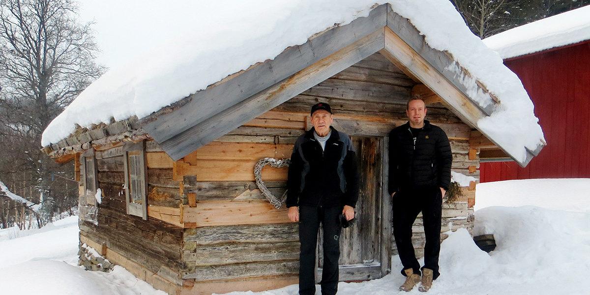 Gunnar Storhaug (t.v.) og sønnen Jonas sørger for at historien til Troli og det lille stedet Beiarn ikke blir glemt. Her foran stabburet på gården. (Foto: Camilla Iversen)