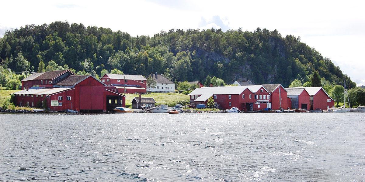På rekke og rad ligger båtbyggeriene på Moen i Risør med Gregersen helt til høyre, så Emmanuel Moen og på venstre side Verner Hansen. (Foto: Einar Engen/Kulturminnefondet)
