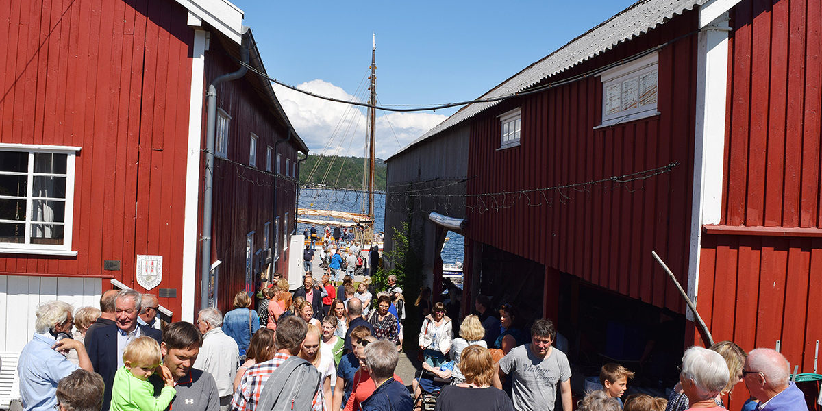 Under trebåtfestivalen i Risør bugner det med folk på Moen. Her mellom buene hos Gregersen. (Foto: Einar Engen/Kulturminnefondet)