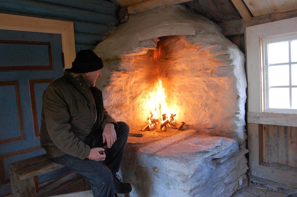 Dette ildstedet er murt med naturstein og leire. Utvendig er overflata kalket. Murverket holder godt på varmen. (Foto: Einar Engen/Kulturminnefondet)