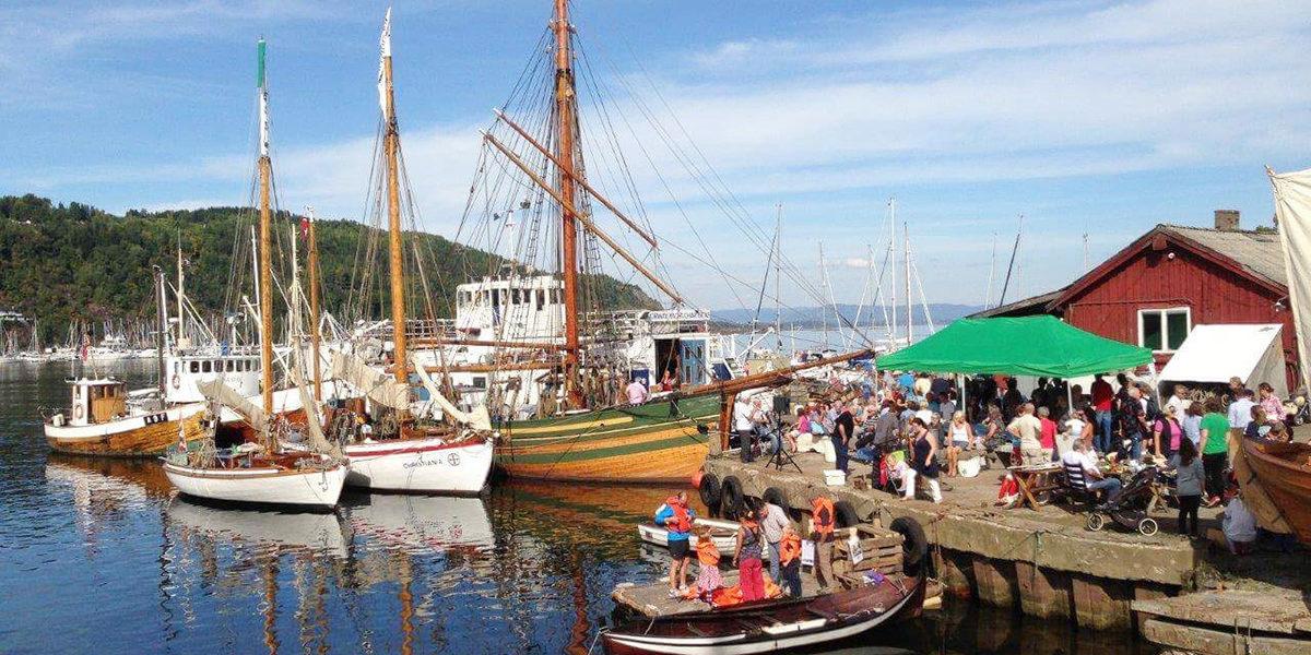 SJ Skreien har fått utført nødvendige arbeider ved Promhavn slipp på Nærsnes i Buskerud. Her ligger hun til kai (båten med høyest mast) ved et arrangement for lokalbefolkningen og tilreisende. (Foto: Norsk Forening for Fartøyvern)
