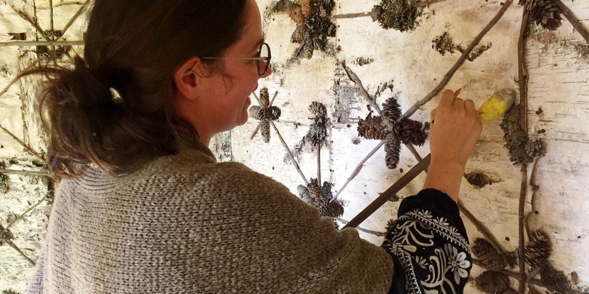 Oppfriskingen av signaturene krevde tålmodighet og en stødig hånd. Dekormaler Stine Aamot stod for arbeider. (Foto: Ellen Jacobsen)