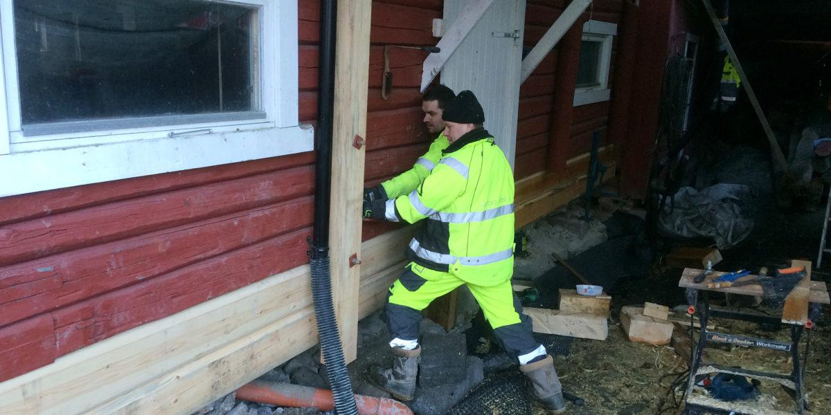 Håndverkerne bytter strevere over muren på tunet på Myhrer gård. (Foto: Trond Myhrer)