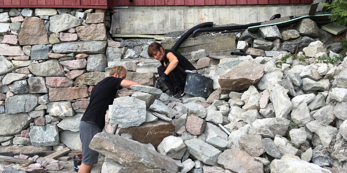 Det lempes og tilpasses stein til muren utenfor møkk-kjelleren. (Foto: Trond Myhrer)