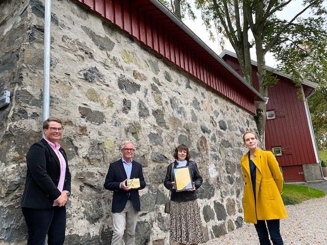Kulturminnefondets styreleder Tine Sundtoft overrekker plaketten til eierne sammen med Riksantikvar Hanna Geiran