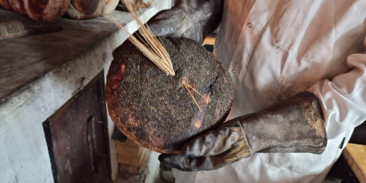 Bakeren med nybakt emmerbrød. Foto: Ingveig Tveranger