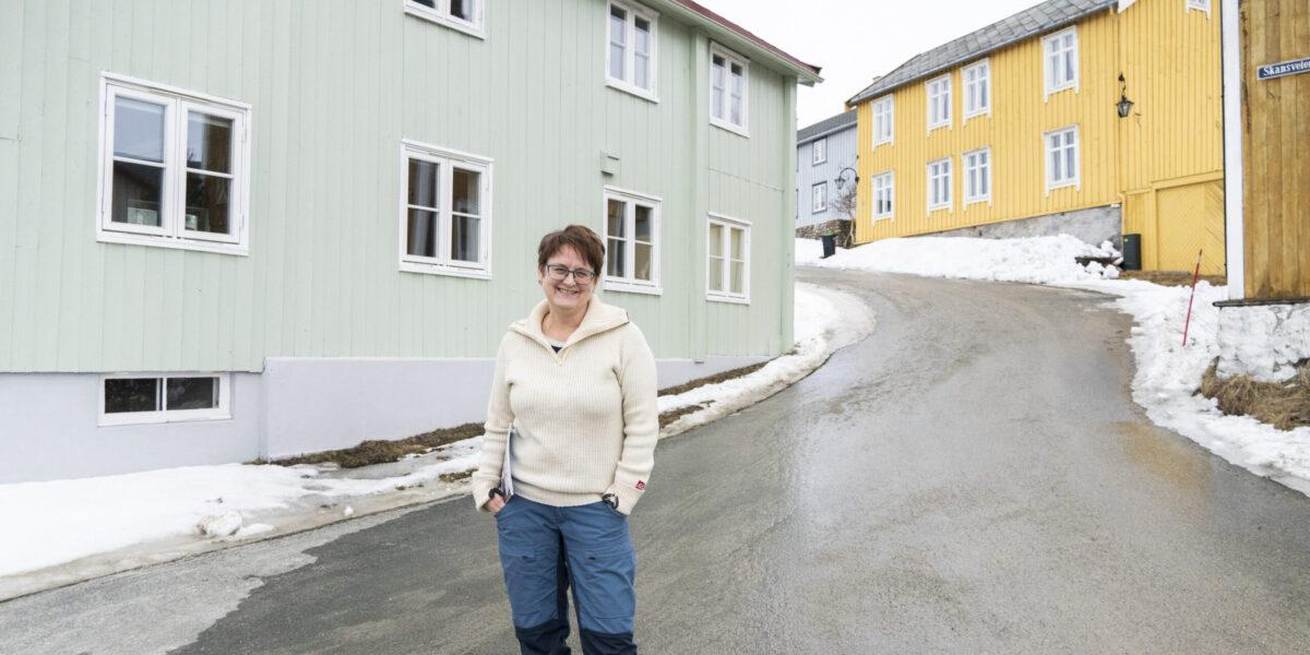 Sigrid Jansen i den pastellfargede gata Skansveien på Røros. Foto: Monica Hägglund Langen/Kulturminnefondet